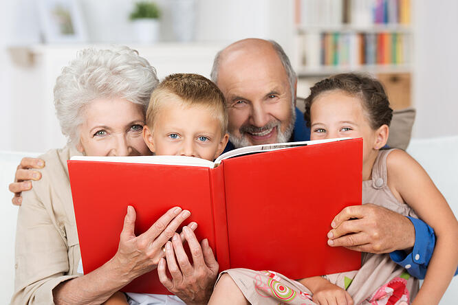 Cute little boy and girl with merry smiling eyes reading with their grandparents peering over the top of the book at the camera