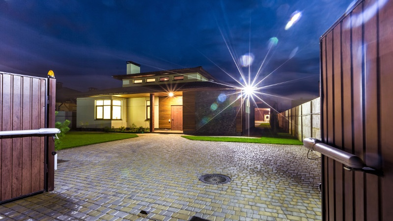 Enbrighten Security Lights illuminate the exterior of the home in the evening time.